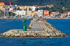 Small green lighthouse at entrance to Carloforte harbor at San Pietro island, Sardinia Royalty Free Stock Images