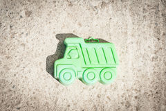 Small green machine on a brown background. Child toy small green machine on a brown background. Toy background concept stock photo