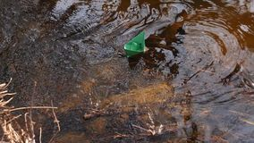 Small green paper boat is flowing along the river. Small green paper boat is flowing along river stock footage