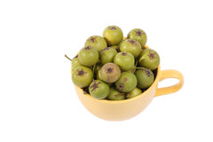 Small green pears in big yellow cup Stock Image