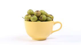 Small green pears in big yellow cup Royalty Free Stock Photo