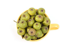 Small green pears in big yellow cup Royalty Free Stock Images
