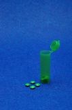 Small green pills with a little green pill bottle Royalty Free Stock Image