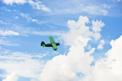 Small green plane flying in blue sky Stock Photography