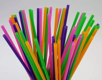 Plastic cup filled with straws. Small green plastic cup filled with colored straws stock image