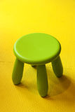 Small green plastic stool for kids isolated on yellow soft floor Stock Photo