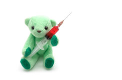 Small green teddy bear holding injection syringe on white backgr Stock Photo