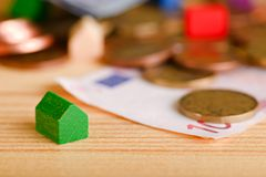 Small green toy house in front of coins and bills Stock Image