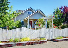 Small grey craftsman style home behind white fence. Stock Photo