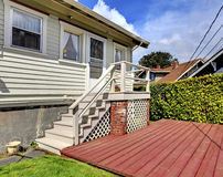 Small grey house with staircase to back yard deck. Stock Photos
