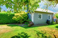 Small grey shed in the sunny green backyard. Stock Photo