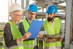 Small group of architects and civil engineers discussing future plans and looking at project documentation. Small group of architects and civil engineers meeting royalty free stock photo