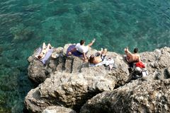 Looking Down on Sunbathers Basking on the Rocks Above the Green Sea Royalty Free Stock Images