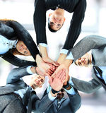 Small group of business people joining hands. Low angle view Stock Image