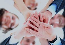 Small group of business people joining hands, low angle view.  Stock Photo