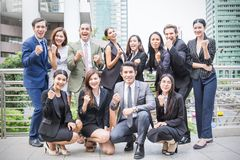 Small group of business people outside their company. Holding hands raised celebrate business success Stock Photography