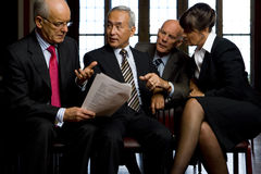 Small group of businessmen and woman discussing paperwork Stock Photos