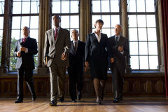 Small group of businessmen and woman walking in hall, low angle view Royalty Free Stock Images