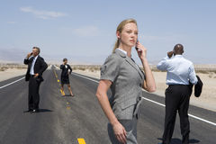 Small group of businessmen and women using mobile phones on road in desert Royalty Free Stock Images
