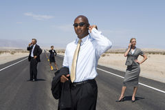 Small group of businessmen and women using mobile phones on road in desert, low angle view Stock Photos
