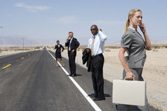 Small group of businessmen and women using mobile phones on side of road in desert, side view Royalty Free Stock Image