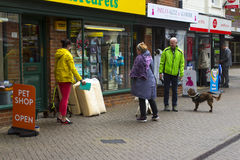 A small group of dog owners meet and chat outside the local pet shop in Hythe in Hampshire on the south coast of England stock photo