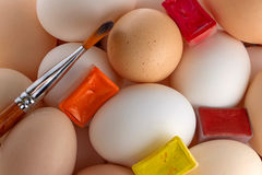 Small group of eggs. Of different colours with Multi-coloured water colour and a brush for drawing Stock Photos