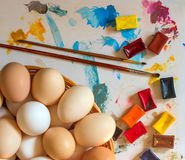 Small group of eggs. Of different colours with Multi-coloured water colour and a brush for drawing royalty free stock photography