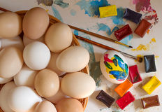 Small group of eggs. Of different colours with Multi-coloured water colour and a brush for drawing royalty free stock image