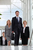 Small group of executives walking up stairs. In a glass roofed atrium royalty free stock photo
