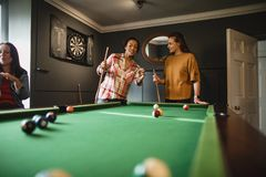 Assessing the Game. Small group of female friends playing a game of pool in a games room in a house stock photos