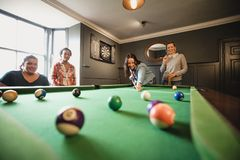Taking the Shot. Small group of female friends playing a game of pool in a games room in a house stock photo