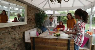 Preparing to Make Lunch. Small group of female friends preparing a healthy lunch inside of a conservatory on a weekend away stock video footage