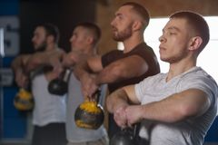 Small Group of Fit Friends Working Out in Gym. Young Athletes Lifting Kettlebells During Workout Session. Sports, Fitness, Teamwork stock photography