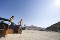 Small group of friends by car in desert, looking at view, low angle view (lens flare) Stock Photo