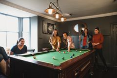 Playing Eight Ball. Small group of friends playing pool in a games room in a house stock photos