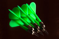 Small group of green darts and it reflection. On black background Stock Images