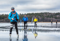 Small group of ice skaters on wet frozen lake. Royalty Free Stock Photo