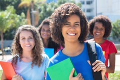Small group of laughing african caucasian and latin female students. In the city in the summer Stock Photography