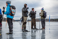 Small group of male ice skaters taking a break on a watery frozen lake. Stock Image