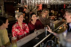 Ladies Night at the Bar. Small group of mature women enjoying a night, sitting at the bar. They are laughing with the young bartender who is making a cocktail stock photography