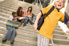 Small Group Of Teenagers (13-15) Studying On Steps Outdoors By Boy (11-13) With Rucksack Stock Image