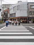 Small group of people crossing the road. Kyoto, Japan - June 27, 2014 : Small group of people crossing the road  in town Stock Images