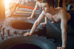 Small group of people doing push-ups on tire. Young athletes working out on beach during a hot summer day. royalty free stock photo