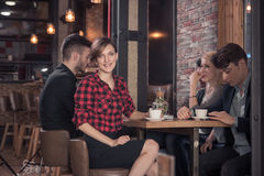 Small group of people, sitting, coffee shop table, woman looking Stock Photos