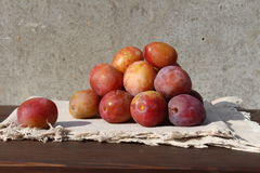 Small group of plums on the wood table. Royalty Free Stock Image