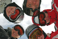 Small group of  snowboarders. Standing in huddle, smiling, low ange view Stock Image