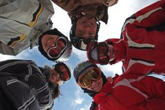 Small group of  snowboarders. Standing in huddle, smiling, low ange view Stock Photography