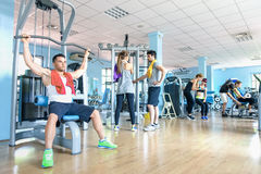 Small group of sportive friends at gym fitness club center. Happy sporty people interacting in weight room training - Social gathering sport concept Stock Images