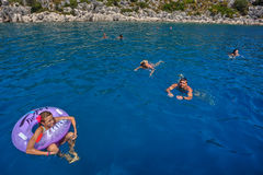 A small group of tourists bathes in the blue sea water. Antalya, Turkey - 28 august, 2014: Several tourists, vacationing in the Mediterranean resort, bathe in stock images
